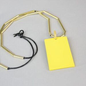 Collana filo nero con tubicini colore oro e piastra in madreperla giallo.