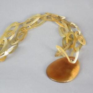 Collana madreperla con anelli ovali uguali beige e ciondolo marrone.
